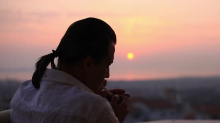 кофе : man watching sunset and smoke cigarette