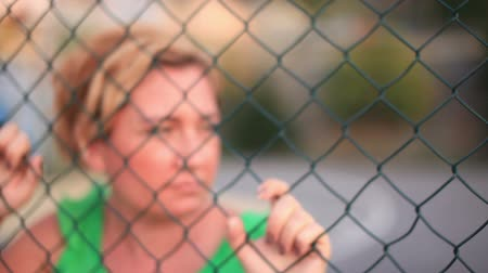 desemprego : woman behind fence wires