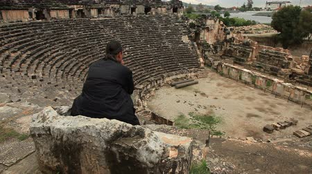 old times : Man sitting on the stone chair in ancient amphitheater Myra Stock Footage