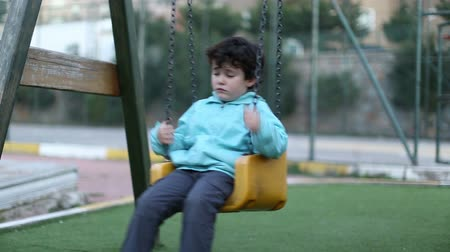 unott : sad little boy on a swing, steady cam shoot