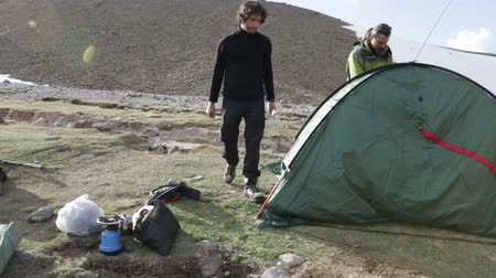 outdoor : Campers pitching a tent at the mountain Stock Footage