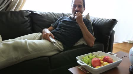 morele : man eating fresh fruit and watching television 1 Wideo