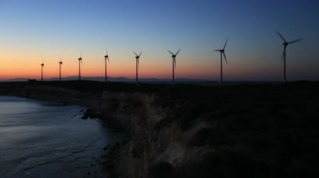 türbin : wind turbines generating clean power with lighthouse at sunset