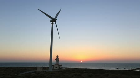 világítótorony : time lapse wind turbines generating clean power with lighthouse at sunset Stock mozgókép