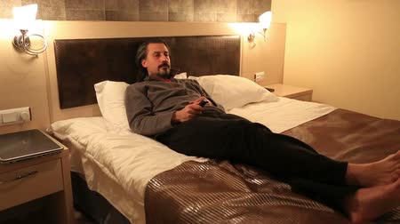 resting : attractive man watching television and use remote control in hotel room