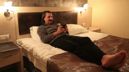 toco : attractive man playing smart phone in hotel room