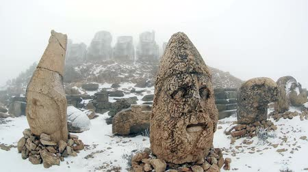 flanked : Commagene Kingdom (Komagene Krallıgı) built on the mountain top a tomb-sanctuary flanked by huge statues at Mount Nemrut Turkey Stock Footage