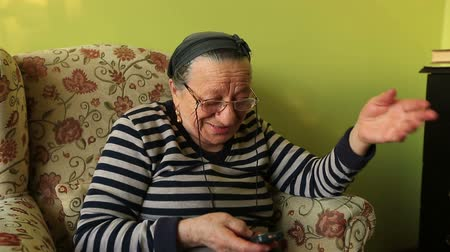 hívó : elderly woman talking on the mobile phone at home
