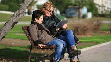 gry komputerowe : mother and son sitting bank and using tablet computer at outdoor