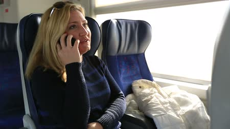 tripping : attractive blonde women talking smartphone in a train