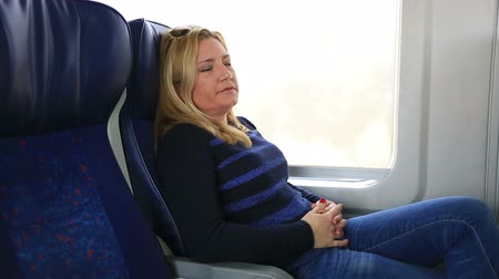 усталый : attractive blonde women trying to sleep in a train Стоковые видеозаписи