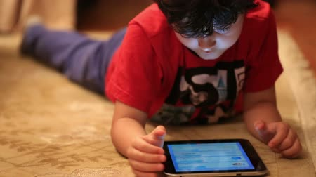 apple computers : little cute kid playing digital tablet in home Stock Footage