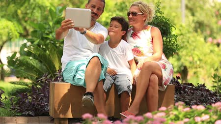 self portrait photography : little happy family taking self portrait in the park Stock Footage