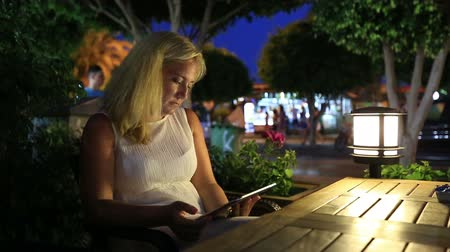 apple computers : attractive blonde women using digital tablet in restaurant at night