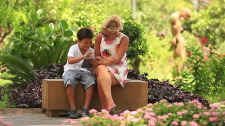 apple computers : mother and son using digital tablet in the park Stock Footage