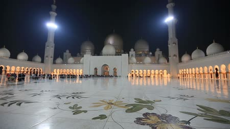 минарет : tourist and muslim people visiting Sheikh Zayed Grand Mosque in Unated Arab Emirates Abu Dhabi at night pan shot