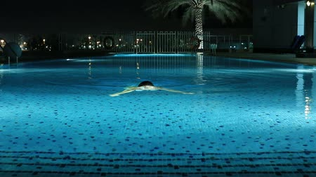 atividades : attractive blonde women swimming a luxury pool at night Stock Footage