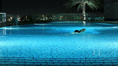 attractive blonde women swimming a luxury pool at night Stock mozgókép