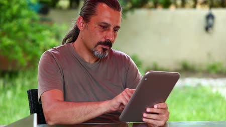 apple computers : middle age brunette man using digital tablet in the garden Stock Footage
