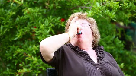 alerji : senior woman using asthma inhaler in a garden