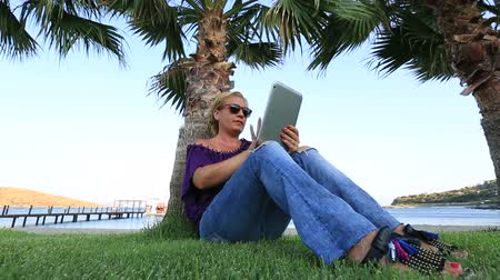 dividir : middle age attractive blonde women using digital tablet at park