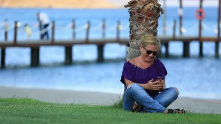 stáří : middle age attractive blonde woman using smartphone at seashore