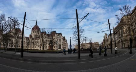 europeu : BUDAPEST, HUNGARY - JANUARY 17, 2019: Yellow tram passes in front of the gothic architecture. Time lapse