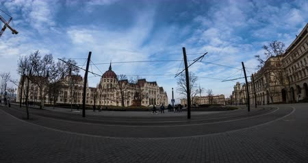 BUDAPEST, HUNGARY - JANUARY 17, 2019: Yellow tram passes in front of the gothic architecture. Time lapse