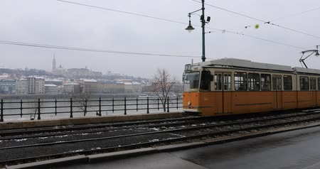 railwayman : Budapest, Hungary, March 15 jan 2019 Old yellow Tram and chain bridge at winter Stock Footage