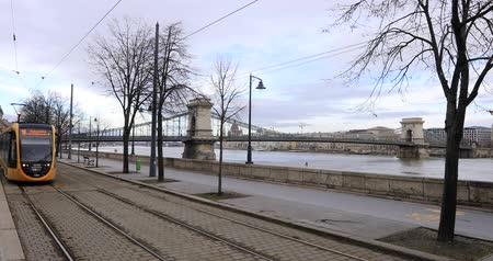 BUDAPEST, HUNGARY - JANUARY 17, 2019: Yellow tram passes near the Danube river at winter time