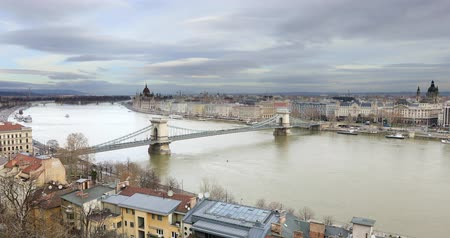 the suspension bridge : BUDAPEST, HUNGARY - JANUARY 16, 2019: Aerial view of buildings, Danube river and old town in Budapest at winter time. Time lapse Stock Footage
