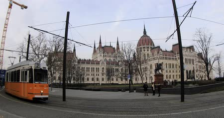 BUDAPEST, HUNGARY - JANUARY 16, 2019: Yellow tram passes in front of the gothic architecture