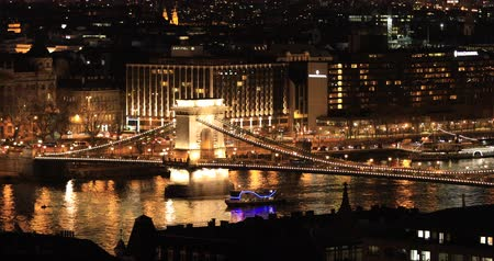 the suspension bridge : BUDAPEST, HUNGARY - JANUARY 17, 2019: A view of the buildings, the Danube river and the Old Town in Budapest. City traffic at night time lapse Stock Footage