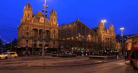 railwayman : BUDAPEST, HUNGARY - JANUARY 17, 2019: A night view of the main facade of the Nyugati Train Station in Budapest. City traffic time lapse
