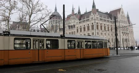 tramwaj : BUDAPEST, HUNGARY - JANUARY 16, 2019: Yellow tram passes in front of the gothic architecture
