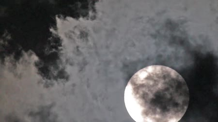 Closeup shot of a full moon moving with the clouds