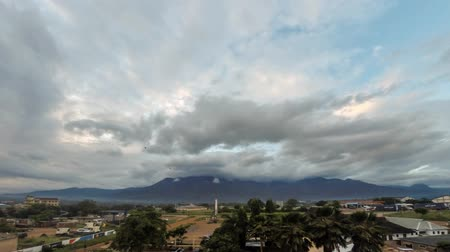 Moving clouds lit by the rising sun, completely covering the Uluguru Mountains in the city of Morogoro, Eastern Region of Tanzania, Africa. Стоковые видеозаписи
