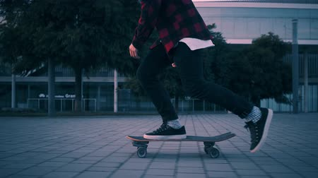 deskorolka : Fashionable rider in hipster red plaid shirt and black jeans just skates on his longboard at twilight time with beautiful paster lightning, camera follows him