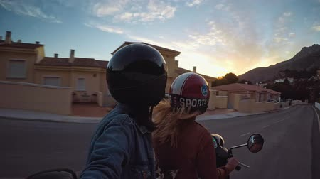 hipster : Two small teenager girls driving their scooter into sunset on small narrow road of mountain village in south of Spain. They are wearing their safe moto helmets and enjoy their ride