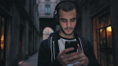 sluch : Smiling and laughing handsome young man listening music from his smartphone in wireless black headphones, dancing on street of old town center in europe at twilight or evening time