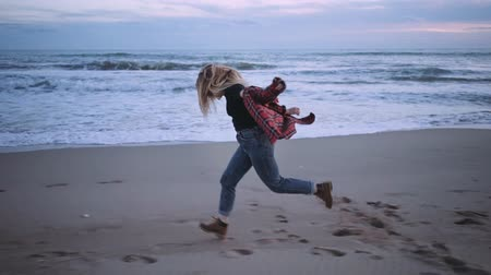 Slow motion video of young successful and beautiful woman running on beach at sunset, happy and excited celebrates winning or just life. Looks ahead into bright future, is proud independent, confident