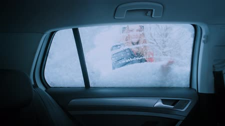 süpürge : Funny cute video of young attractive woman clean passenger window of car from snow and ice after blizzard or snow. Winter commuting concept in harsh cold conditions. looks inside and smiles Stok Video