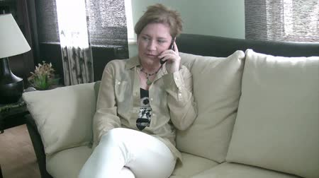 conversando : Woman sitting on sofa talking on phone