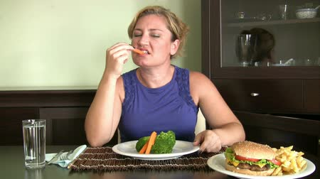 calorias : Hungry women looking two plate and choosing one of them