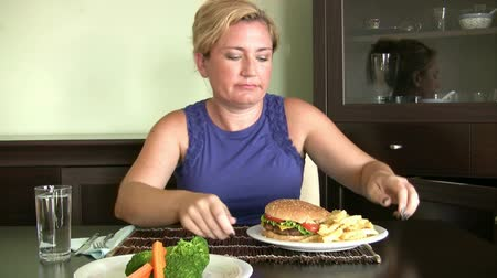 диета : Hungry women looking two plate and choosing one of them