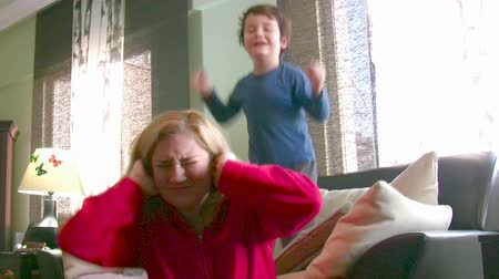 усталый : Noisy energetic little boy and tired mom Стоковые видеозаписи