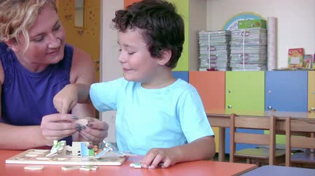 preschool : Preschool Student solving puzzle with his teacher Stock Footage