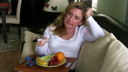 calorias : Woman watching tv and eating fruit