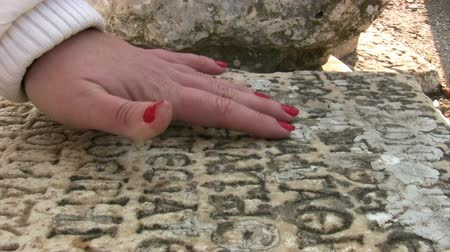 sarcophagus : Woman hand touching ancient Greek inscriptionncient stone