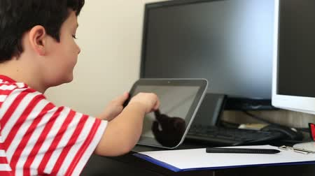 házi feladat : Young student doing homework with his digital tablet